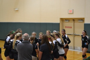 Mr. Kellerman and Ms. Leonard observe as the coach talks to the Varsity Volleyball team